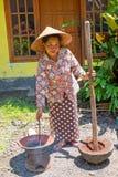 JAVA, INDONESIEN - 21. DEZEMBER 2016: Grainding Kaffeebohnen der lokalen Frau in Indonesien Stockbilder