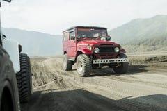Java, Indonesien März, 24, 2016: Roter Jeep 4x4 für Touristen am Kessel von Vulkan Berg Bromo, der aktive Berg Bromo ist einer vo Stockbild