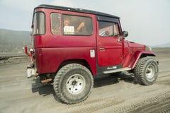 Java, Indonesien März, 24, 2016: Roter Jeep 4x4 für Touristen am Kessel von Vulkan Berg Bromo, der aktive Berg Bromo ist einer vo Stockfotografie
