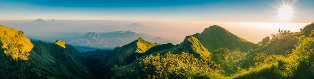 Java province in Indonesia. Panoramic photo of mountains and Mount Merbabu covered with sunlight and fog during sunrise near Yogya in central Java province in Stock Photography