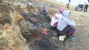 Javanese sulfur miners sitting atop active Kawah Ijen volcano. royalty free stock image