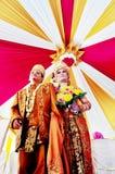 Javanesse回教新娘穿戴beskap和新郎佩带在传统婚礼的蜡染布 免版税库存图片