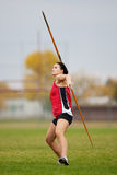 Javelin athlete. Female athlete throwing a javelin at a track and field sports event stock images