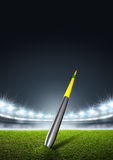 Javelin In Generic Floodlit Stadium. A javelin pegged into the turf of a generic stadium with a green grass pitch at night under illuminated floodlights royalty free illustration