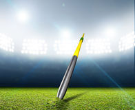 Javelin In Generic Floodlit Stadium. A javelin pegged into the turf of a generic stadium with a green grass pitch at night under illuminated floodlights royalty free stock photography