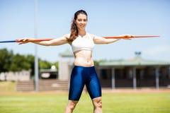 Javelot de transport heureux d'athlète féminin sur son épaule Images stock