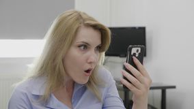 Jaw dropped office woman surfing on social media network using smartphone staring in shock watching something disturbing - stock footage