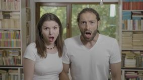 Jaw dropping reaction teenage couple watching something scary and unbelievable looking thrilled and astonished with open mouth -. Jaw dropping reaction from stock footage