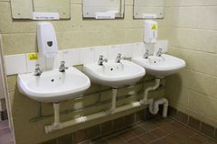 Jawnych toalet wc rząd baseny ostrzega gorącą wodę i no pije woda znaka fotografia stock