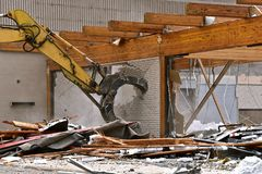 Jaws of an excavating machine destroy a brick wall. The jaws of an excavating machine destroy the brick wall in a demolition project stock photography