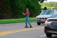 Jaywalking distracted cell phone user pedestrian. A man who is completely distracted by his cell phone is unaware that he is jaywalking by walking out into heavy Royalty Free Stock Images