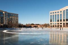 Jazda na łyżwach lodowisko na zamarzniętym jeziorze między budynkami biurowymi Obraz Stock
