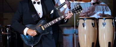 Jazz band performance. Close-up. An abstract man in a strict suit plays the guitar on the scene in the foreground. Drums in the stock photo