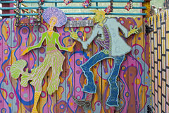 Jazz Dancers. Funky Jazz Man and Woman Dancers are Hanging on a Blue Yellow and Pink Abstract Painted Picket Fence Dancing to Music Stock Images