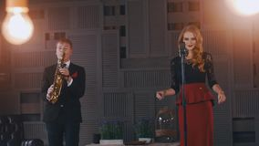 Jazz duet perform on stage. Saxophonist in suit. Vocalist in retro style. Artist. Lights. Click fingers stock footage