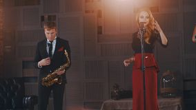 Jazz duet perform on stage. Saxophonist in suit. Vocalist in retro style. Artists stock video