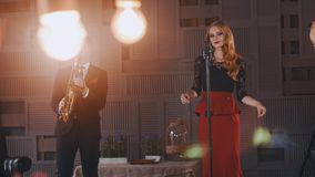 Jazz duet perform on stage. Saxophonist in suit. Vocalist in retro style. Music