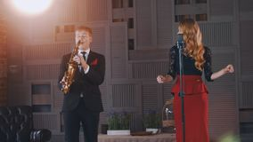 Jazz duet perform on stage. Saxophonist and vocalist. Retro style. Dance. Lights. Click fingers stock video