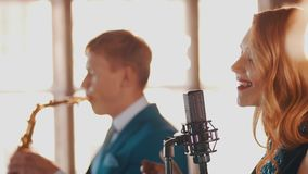 Jazz duet on stage of restaurant. Vocalist at microphone. Saxophonist. Style. Jazz duet on stage of restaurant. Vocalist at microphone. Saxophonist. Retro style stock video footage