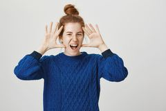 Jazz hands never come out of style. Portrait of emotive good-looking female with red hair combed in bun hairstyle. Shouting or roaring with palms near head Royalty Free Stock Image
