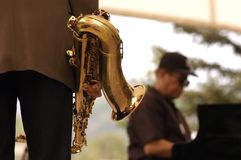 Jazz Horn - Music 2. Horn being held with piano player in the background, focus on the horn Royalty Free Stock Photos