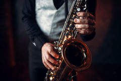 Jazz man hands holding saxophone closeup. Brass band musical instrument. Solo jazz-man with sax in studio Royalty Free Stock Photos