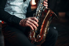 Jazz man hands holding saxophone closeup. Brass band musical instrument. Solo jazz-man with sax in studio Stock Photo