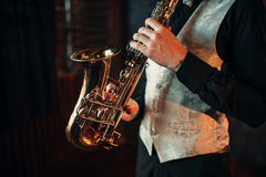 Jazz man hands holding saxophone closeup. Brass band musical instrument. Solo jazz-man with sax in studio Royalty Free Stock Image