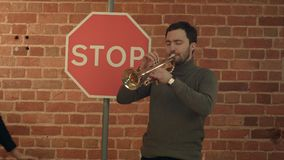Jazz man playing his Trumpet with Road sign STOP. Professional shot in 4K resolution. You can use it e.g. in your commercial video, business, presentation Stock Images