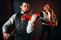 Jazz man and violinst, classical musical duet. Jazz men and violinst, classical musical duet. Sax and fiddle music players Stock Photography