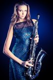 Jazz music. Portrait of a sexual young woman posing with saxophone at studio Royalty Free Stock Photos