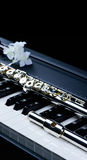 Jazz music instrument flute and piano keyboard close up with   flower. Jazz music instrument flute and piano keyboard close up with flower  on black background Royalty Free Stock Photography