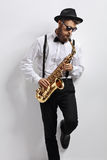 Jazz musician leaning against a wall and playing saxophone Stock Photography