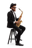 Jazz musician with a saxophone sitting on a chair Royalty Free Stock Photos