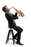 Jazz musician seated on a chair playing a saxophone Royalty Free Stock Photo