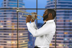 Jazz performance in megalopolis. Enthusiast with a trumpet. Jazz performance in megalopolis. Impressive musician has skills. The view from studio window stock photography