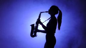 Jazz performed by musician girl playing saxophone. Silhouette, slow motion stock footage
