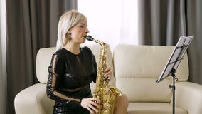 Jazz saxophone player performing on the sax in the living room. Rehearsing for the concert stock footage