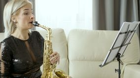 Jazz saxophone player performing on the sax in the living room. Rehearsing for the concert stock video