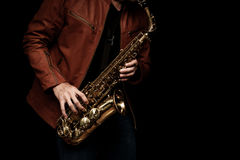 Jazz saxophone player on the stage. Male jazz saxophone player on the stage with brown leather jacket Royalty Free Stock Photo