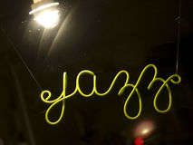 Jazz Sign. A green neon sign saying jazz hanging in a store window lit by a single spotlight Stock Photos