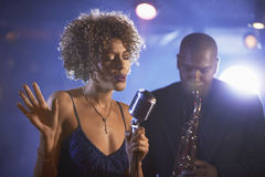 Jazz Singer And Saxophonist In Performance. Female singer and saxophonist performing at the jazz club Royalty Free Stock Image