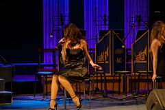 Jazz singer. sexy woman in black cocktail dress singing while sitting on chair at stage with mic. elegance and look. fashion and b stock images