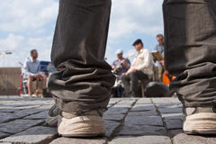 Jazz street performance. Image of a boy's legs as he is looking to a Jazz street band performing Stock Photography