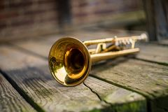 Jazz Trumpet Club. Old rusty Jazz instrument trumpet leaning against brick wall building outside club royalty free stock photos