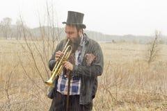 Jazz Trumpet Gypsies. Stylish bearded gypsy plays trumpet on a wilderness path Stock Image