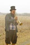 Jazz Trumpet Gypsies. Stylish bearded gypsy plays trumpet on a wilderness path Royalty Free Stock Image