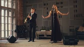 Jazz vocalist in dark dress perform on stagew with saxophonist in suit on stage stock video footage
