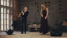 Jazz vocalist in dark dress and saxophonist in black suit perform on stage. Duet stock video footage