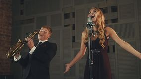 Jazz vocalist in dark dress and saxophonist in suit perform on stage. Dancing. Elegance. Retro style stock footage